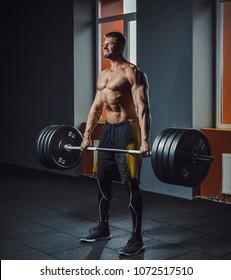 european caucasian athletic man doing deadlift with heavy barbell.