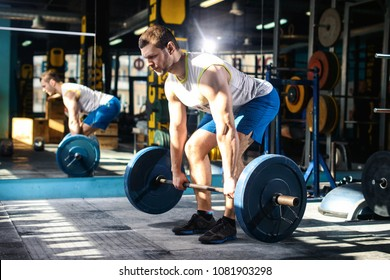 European caucasian athletic man doing deadlift with heavy barbell. man lifting barbell opposite window. Moment of lifting weight. Healhy lifestyle, fitness, crossfit and bodybuilding