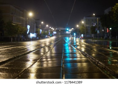 European city in the evening in autumn, the old tram tracks after wet from the water after the rain, blurred background of the empty street in the dark lights Shine