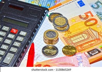 European coins and banknotes, a calculator and a ballpen for creating a calculation