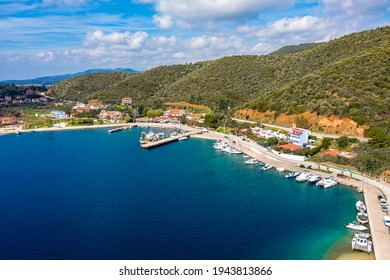 European country village on Mediterranean sea shore with coastline pier for fishing boats. Small resort town with holiday villas along green forest hills summer background