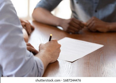 European couple during meeting with african ethnicity realtor signing rental agreement close up image, client buying first property hold pen put signature on legal paper document, make deal concept