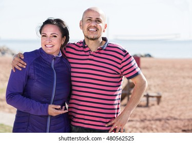 european  couple smiling holding each other on the beach