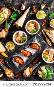 European cuisine. appetizer for wine on a black background. Pate, mini salad, canape, sea products, salmon and mussels in tomato sauce. Top view, copy space