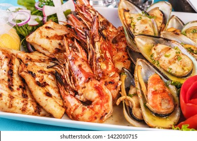 European cuisine, Mediterranean dish. Plate with assorted sea grill. Fried fish, king prawns with lemon, mussels with oyster sauce, colmar rings, crab meat