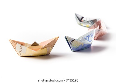 european currency bills folded to sailboats, arranged as a curve