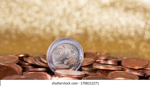 European currency. Coins on a gold background. Gold bokeh. A standing coin. Cash money.