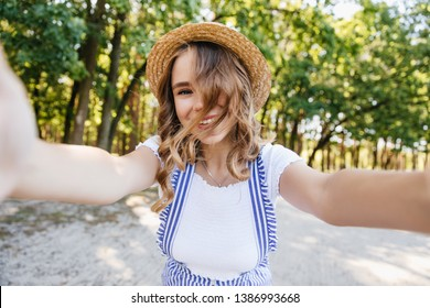 European cute girl with wavy hair playfully posing in park. Emchanting lady in hat making selfie with trees on background.