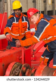 European deck officer wearing orange overall and red hardhat working together with African sailor wearing orange overall and yellow hardhat on red deck of a ship during mooring operation