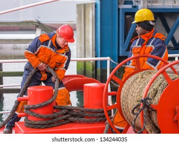 European deck officer wearing orange overall and red hardhat working with ropes together with African sailor wearing orange overall and yellow hardhat on red deck of a ship during mooring operation