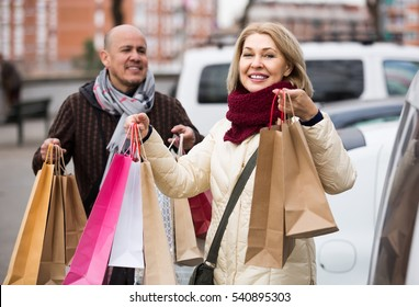 european elderly couple carrying purchases and smiling outdoors. focus on woman