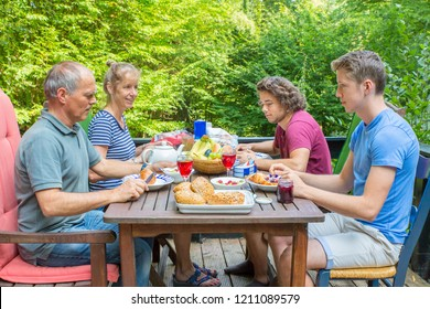 European family eating lunch on terrace in nature