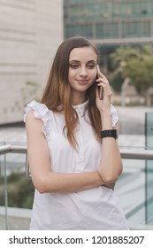 European female with brown hair, in white blouse and with black leather watches making a phone call with positive emotion. Mobile phone connection concept