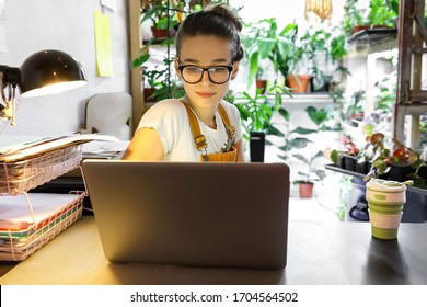 European female gardener in glasses using laptop, scrolling through social networks, reads news, coffee/tea mug on table, home garden/greenhouse on background. Cozy workplace, remote work
