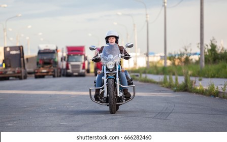 European female motorcyclist driving on chopper motorbike on asphalt highway, front view