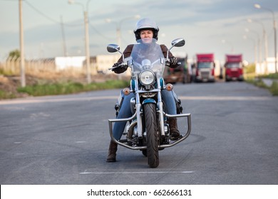 European female motorcyclist sitting on a classic chopper on an asphalt road, front view