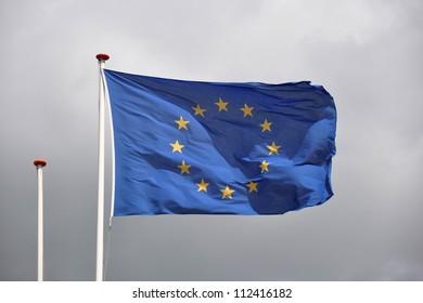 European flag in grey clouded sky