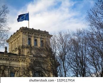 European flag waving on the roof of the berliner Bundestag over blue sky