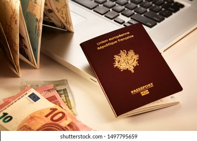 European, french passport leaning on a laptop computer by a map and some european money