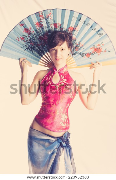 European girl dressed as Japanese geisha with a big blue fan in her hands vintage photo stylized.