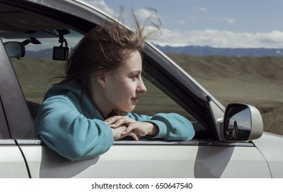 The European girl goes in the car having put out the head in a window