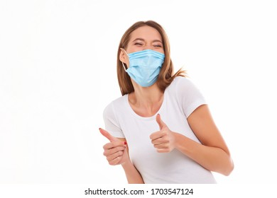 European girl in a medical mask, shows thumb up. Conceptual photo on the theme of the Covid 2019 pandemic. Isolated on a white background.