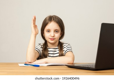 A European girl is sitting at a table doing her homework. Online training through zoom. Distance learning.
