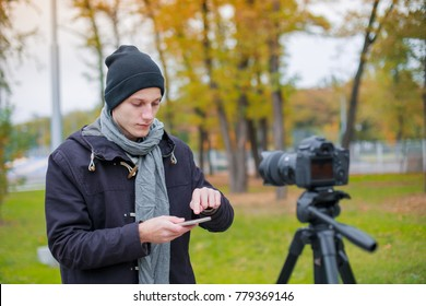 European guy stands opposite the camera on a tripod and uses a mobile phone. Outdoors.