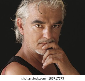 European handsome man with grey hair,mustache and goatee, wearing black undershirt, with the hand touching his chin, having a deep thoughtful look, over black background