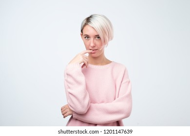 European happy flirty coquettish woman looking up at camera. young beautiful girl with dyed hair on white background.
