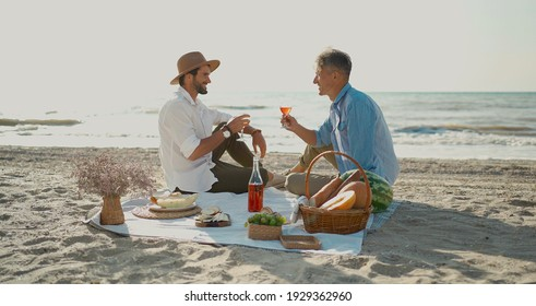 European happy gay couple drinking wine and enjoying romantic picnic at beach. Homosexual relationships and alternative love lifestyle concept
