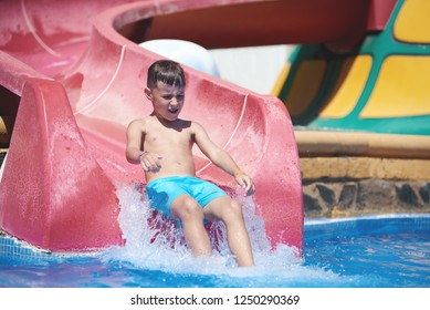 European kid is having fun in the waterpark. He is gliding from the water slide.