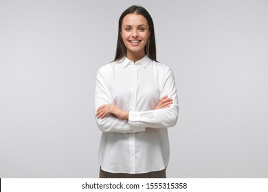 European lady standing with arms crossed, showing she is ready to guide and support, isolated on gray background