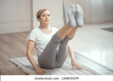European Looking Woman Over 50 Years Old Doing Yoga at Home in the Living Room. Yoga is Good For Health. A Woman Keeps Herself in Shape Thanks to Her Yoga Classes.