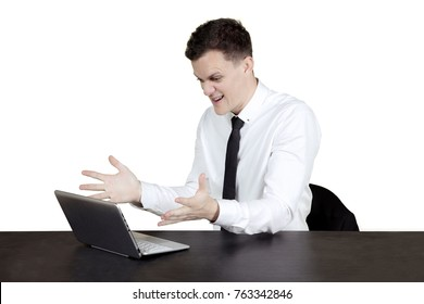 European male entrepreneur looks angry while working with a laptop, isolated on white background
