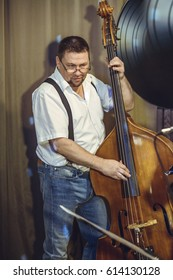 A European male middle-aged, plays a restaurant on a contrabass on stage.