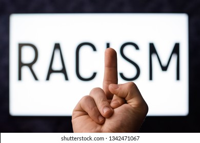 European male showing middle finger to inscription Racism on a screen in order to show his attitude towards racists