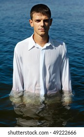 european man in classic white shirt in the sea waters
