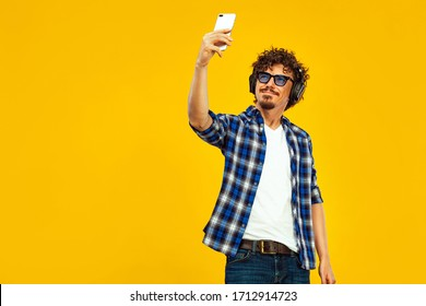 European man with curly hair in blue sunglasses with mobile phone or smarphone. Handsome smiled stylish hipster in plaid shirt posing over yellow background.