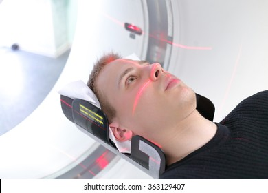 European man are entering brain with CT scan in hospital room