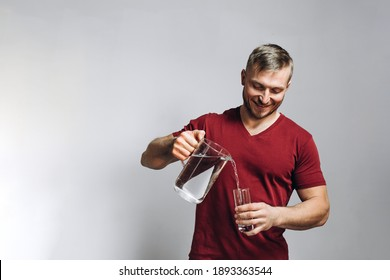 A European man pours water into a glass. Portrait of a man with water on a light background. High quality photo