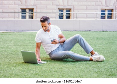 European Man studying, working in New York, with beard, little gray hair, wearing white Polo shirt, gray pants, white sneakers, sitting on green lawn, working on laptop computer, texting on cell phone