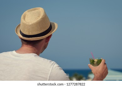 European Man in sunhat with glass of long drink cocktail. He is standing on the hotel's balcony and enjoying picturesque view.