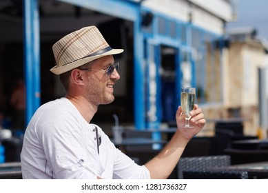 European man in sunhat is sitting at the city cafe and drinking champagne. He is celebrating something.