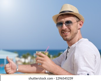 European Man in sunhat and sunglasses with glass of long drink cocktail. He is standing on the hotel's balcony enjoying picturesque view and smoiling to the camera.