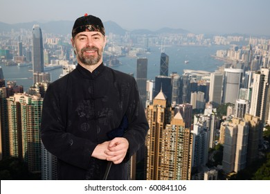 European man in traditional Chinese costume at the Victoria peak in Hong Kong