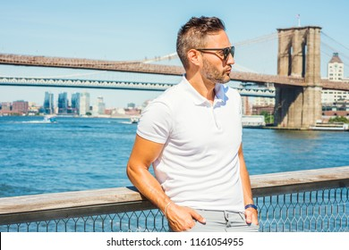 European Man traveling in New York, with beard, little gray hair, wearing white Polo shirt, sunglasses, standing by East River, looking around, thinking. Manhattan, Brooklyn bridges on background.