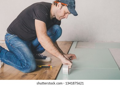 European man working at home - laying polystyrene substrate for laying laminate