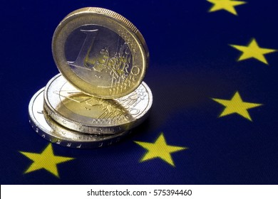 European metal cash money. . Three euro coins. One euro coin is standing on two two euro coins. European community flag as a background. Macro image.