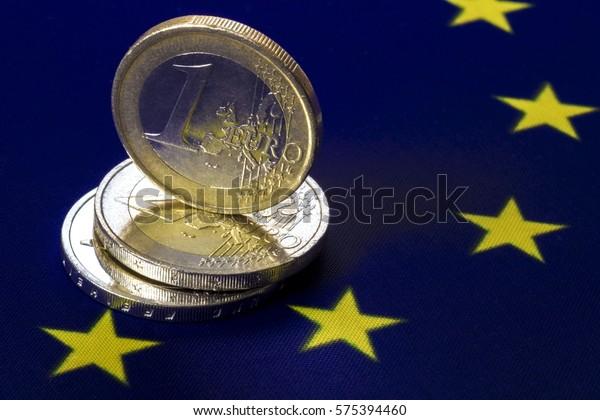 monnaie européenne en métal. . Trois pièces en euros. Une pièce en euros se tient sur deux pièces en euros. Le drapeau de la communauté européenne en arrière-plan. Image macro.